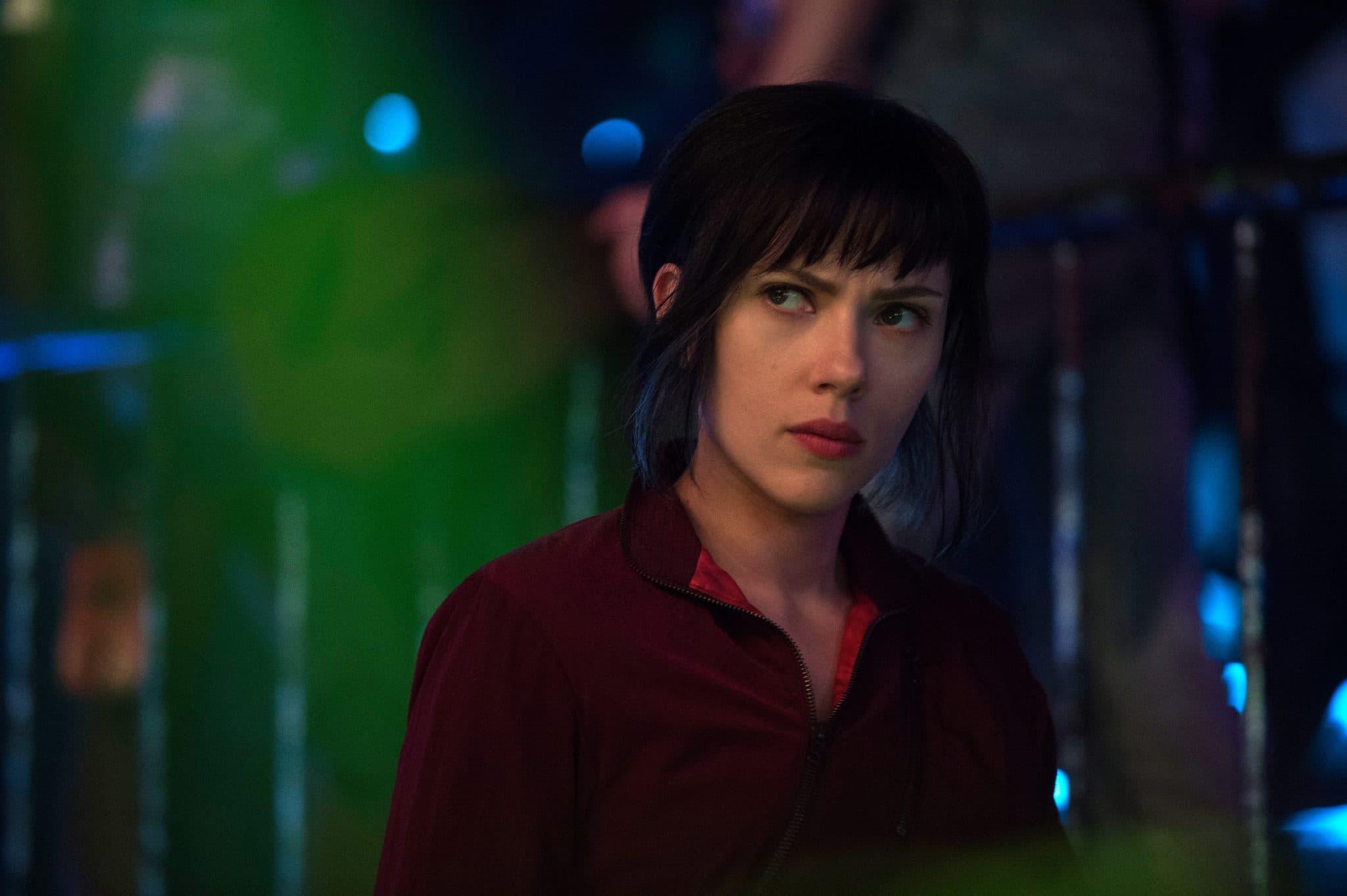 Scarlett Johansson aus Ghost in the Shell trägt eine schwarz gefärbte Kurzhaarfrisur sowie ein rotes Oberteil. Sie schaut skeptisch an der Kamera vorbei, der Hintergrund zeigt verschwommene bunte Lichter. Scarlett Johannsson wurde für die Rolle der Frankenstein's Braut gecastet - unser Filmtoast Newsbrunch.