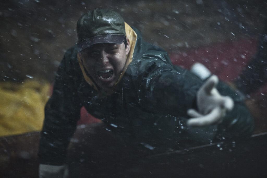 Park Yoochun streckt seine Hand in Richtung Kamera aus und schreit laut. Im Hintergrund prasselt der Regen.