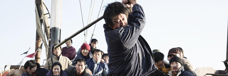 Kapitän Kang Cheol-joo (Kim Yoon-seok) steht auf dem Schiffsdeck und schlägt mit einem Stab auf jemanden oder etwas ein. Im Hintergrund schauen viele Menschen erschütternd zu.