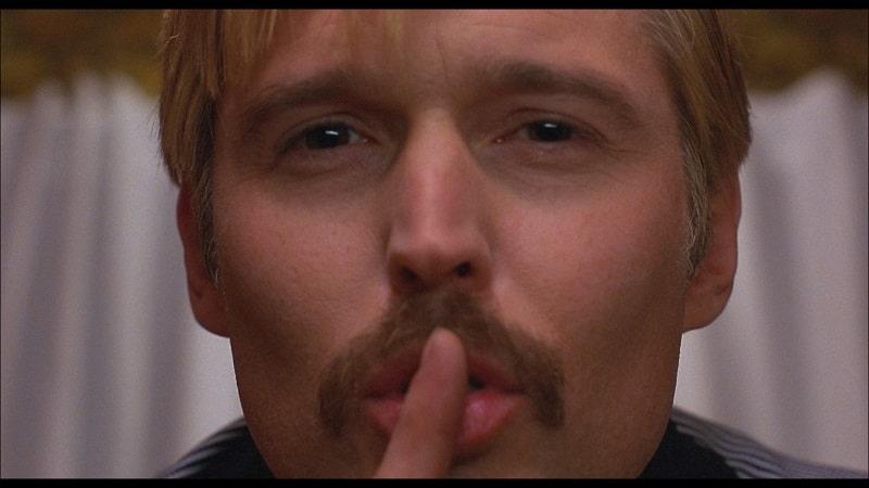 Der Coach signalisiert mit dem Zeigefinger auf dem Mund, dass etwas geheim bleiben soll in Mysterious Skin