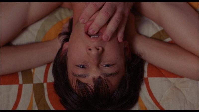 Neil Liegt auf dem Bett, die Arme hinter sich verschränkt, während eine männliche Hand nach seinem Mund tastet in Mysterious Skin