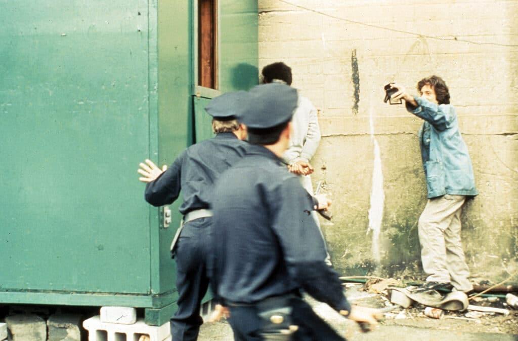 Frank Serpico steht in Zivilkliedung an der Wand und zeigt zwei Polizisten seine Dienstmarke, während ein Mann mit Handschellen neben ihm steht