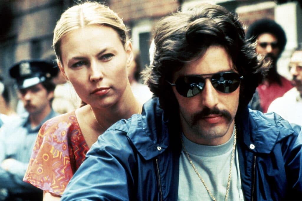 Serpico und seine Freundin fahren auf dem Motorad durch die Straße. Im Hintergrund sieht man einen Polizisten und weitere Menschen