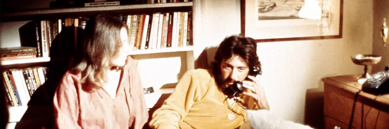 Serpico liegt auf dem Bett und telefoniert, während seine Freundin neben ihm auf dem Bett sitzt und sein Bein hält