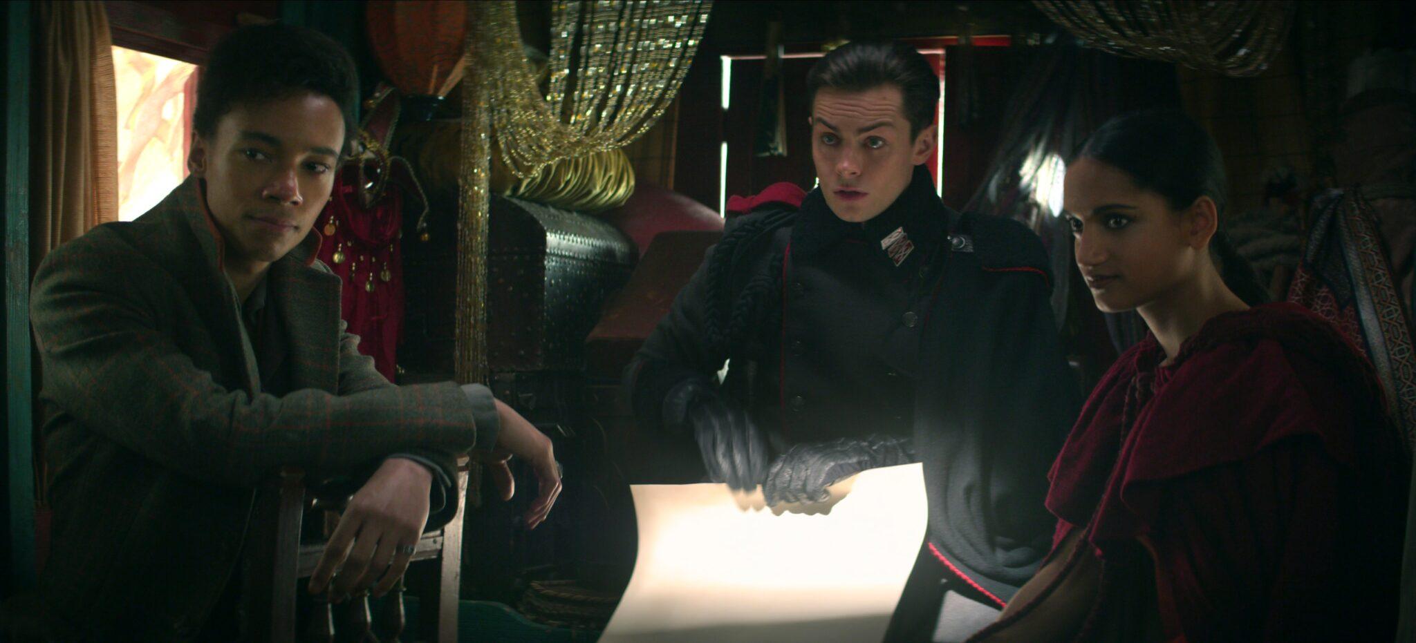 Jesper, Kaz und Inej (von links nach rechts) sitzen in einer Kutsche. Alle tragen dunkle Kleidung und schauen eher ernst und besorgt drein. In der Mitte hält Kaz in seinen Händen einen Bogen Papier.