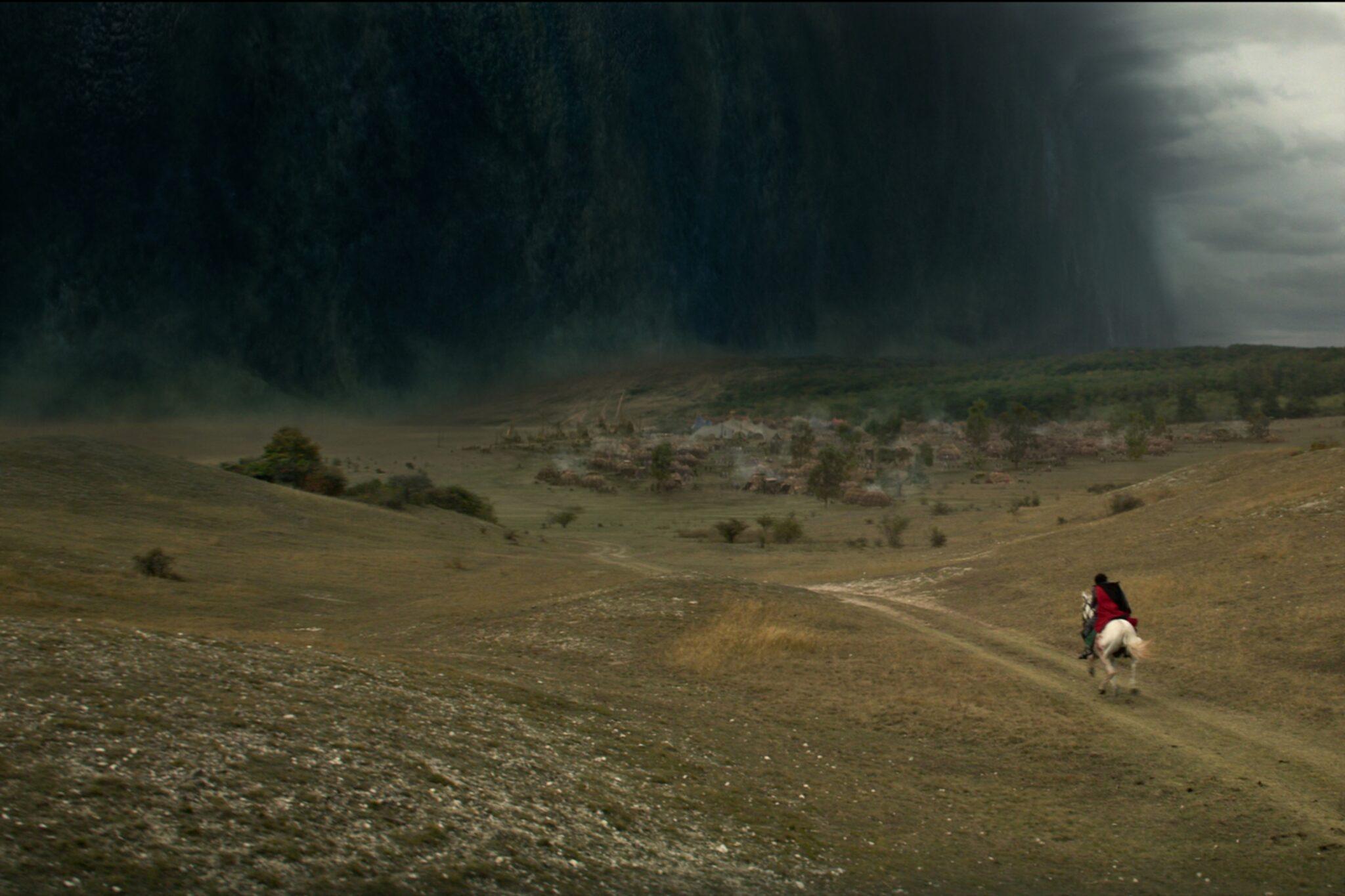 Eine Reiterin mit rotem Umhang auf weißem Pferd reitet in Richtung einer dunklen Nebelwand, der Schattenflur.