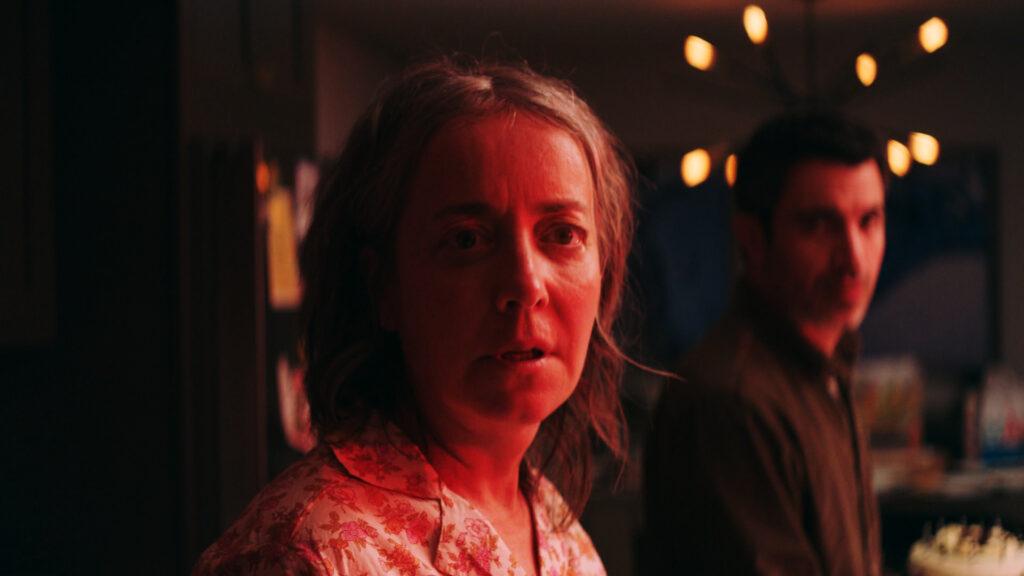 Jane Adams schaut im Pyjama betroffen in die Kamera. Im Hintergrund Chris Messina als Janes Bruder Jason.