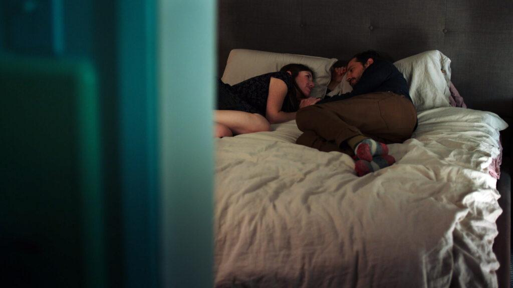Amy und Craig liegen auf dem Bett und schauen sich an in She Dies Tomorrow.