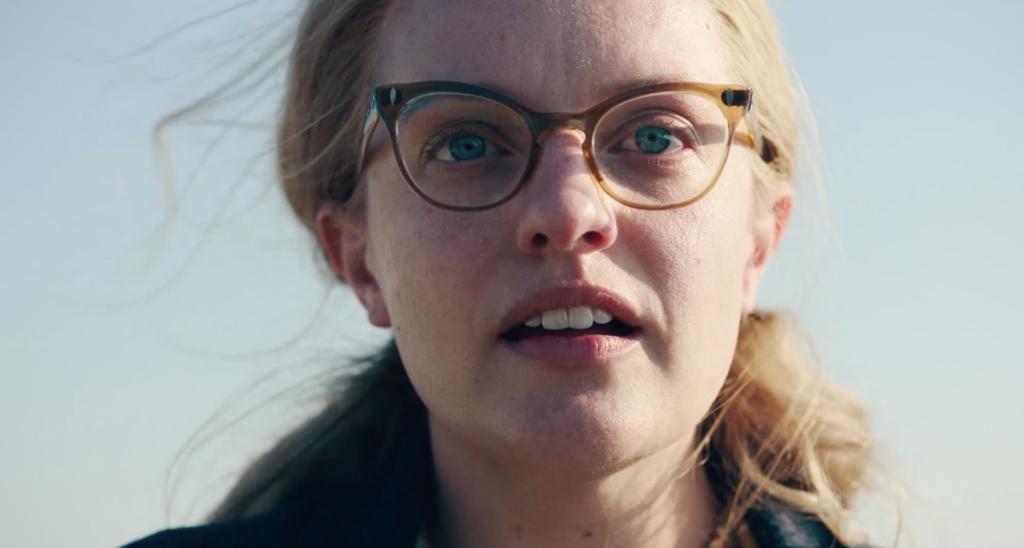 Eine Frau mit Brille, dargestellt von Elisabeth Moss, schaut neben der Kamera her