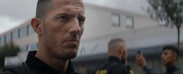 """Auf dem Bild ist die Kontrolle eines Unruhestifters zu sehen. Besonders ist Jan Høyer (Simon Sears) in Großaufnahme zu sehen. Dieser blickt skeptisch in seine Umgebung. Im Hintergrund ist der Kollege Mike (Jacob Lohmann) bei der Vernehmung zu sehen. - """"Shorta - Das Gesetz der Straße"""""""