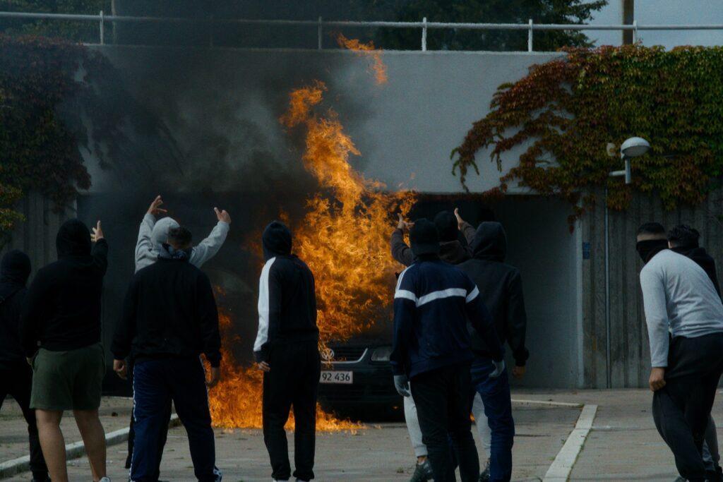 """Auf dem Bild ist zu erkennen, wie die ituation eskaliert. Einige scheinbar Jugendliche haben ein Auto in Brand gesteckt und blicken, mit dem Rücken zum Betrachter, auf das brennende Auto. - """"Shorta - Das Gesetz der Straße"""""""