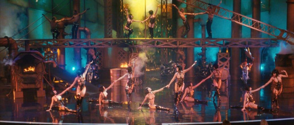 """""""Showgirls"""" bietet einige Imposante Bilder von der Bühnenshow. Auf dem Bild sind viele halbnackte Tänzerinnen und Tänzer in schwarzen, beinahe nicht existenten, Lederkostümen. Dazu ist auf der Bühne eine Stahlkulisse aufgebaut auf der weitere Tänzerinnern zu sehen sind."""