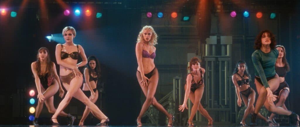 """Nomi (Elizabeth Berkley) tanz in """"Showgirls"""" für die große Show """"Goddess"""" vor. Lediglich mit BH und Strumpfhose bekleidet tanzt sie neben mehreren anderen Kandidatinnen."""