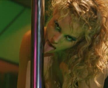 """Nomi (Elizabeth Berkley) bei einer Tanznummerin """"Showgirls"""". In Einem Stripclub leckt sie die Tanzstange ab und blickt sehr lustvoll auf jemanden im Publikum."""