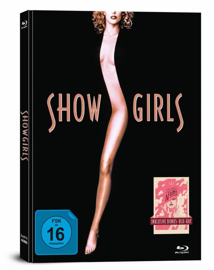"""Das deutsche Blu-ray-Mediabook Cover von """"Showgirls"""" ist sehr schlicht gehalten. Das Cover ist größtenteils in schwarz gehalten. Zentral steht der Schriftzug Showgirls. Das Show und Girls wird zentral geteilt durch ein Bild von Nomi (Elizabeth Berkley). Zu sehen ist aber nur ihre linke Seite von Kopf bis Fuß, welche sich vom oberen bis unteren Rand des Covers zieht. Rechts unten ist zudem ein rosa farbiger Klecks auf beigen Hintergrund zu sehen. Dieser stellt das Cover der beigefügten Dokumentation """"You Don't Nomi"""" dar."""
