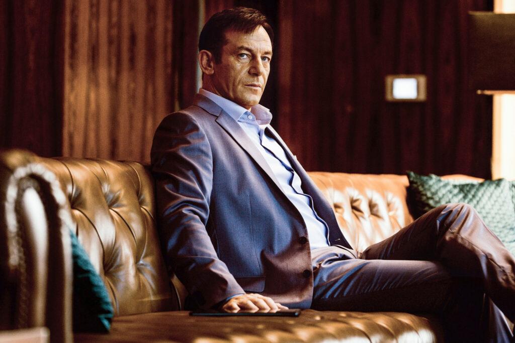 """Auf dem Bild ist Jason Isaacs in """"Skyfire"""" zu sehen, der auf einer braunen Ledercouch sitzt. Er trägt einen blauen Anzug und blickt zu seiner rechten Seite ohne jegliche Mimik auf etwas außerhalb des Bildes."""