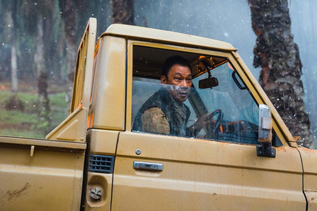 """Auf dem Bild ist Xueqi Wang in """"Skyfire"""" zu sehen, der hier am Steuer eines Geländewagen sitzt und panisch bei halb runtergelassenen Fenster aus dem Auto schaut."""