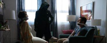 Zwei Opfer sitzen sich gefesselt gegenüber, dazwischen der schwarz gewandete Druide in Slasher: Solstice