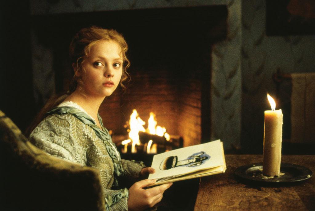 Christina Ricci in Sleepy Hollow als Katrina Van Tassel sitzt vor dem Kamin und liest ein Buch als jemand hereinkommt und sie sich zu diesem umdreht.