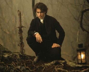 Johnny Depp kniet auf einem Bein nieder und begutachtet ein Schwert, das in den Boden gerammt ist. Das Schwert ist von Ranken umschlungen.
