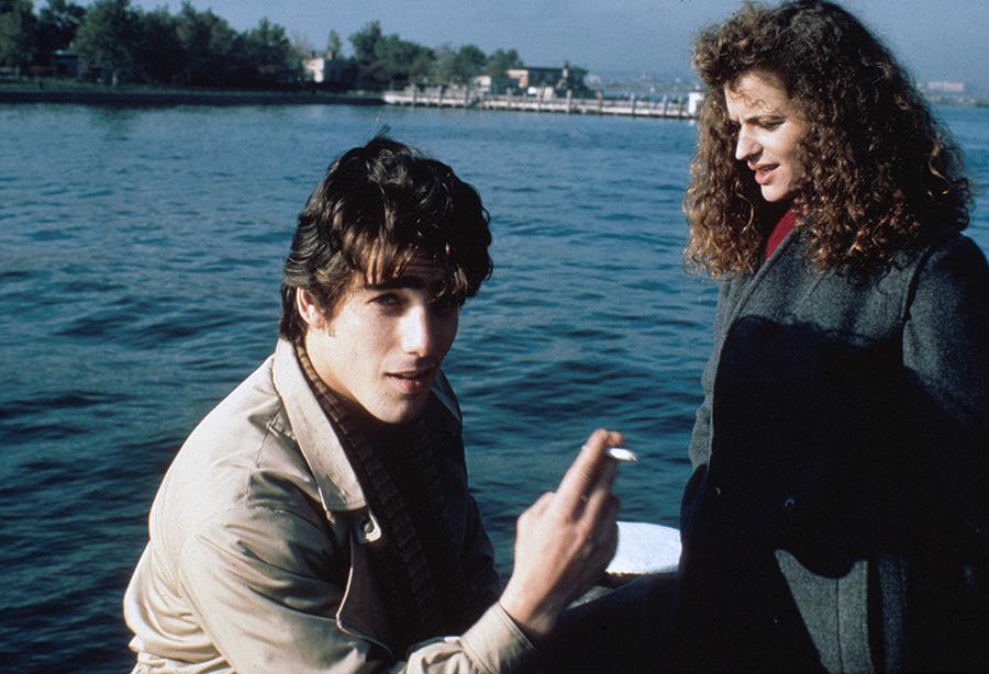 Der Söldner sitzt auf einem Boot und hält eine Zigarette in der rechten Hand. Ihm gegenüber steht eine Frau auf der rechten Bildseite und hält den Blick linksseitig gesenkt. Im Hintergrund ist das Meer und Festland in der oberen Bildhälfte erkennbar.