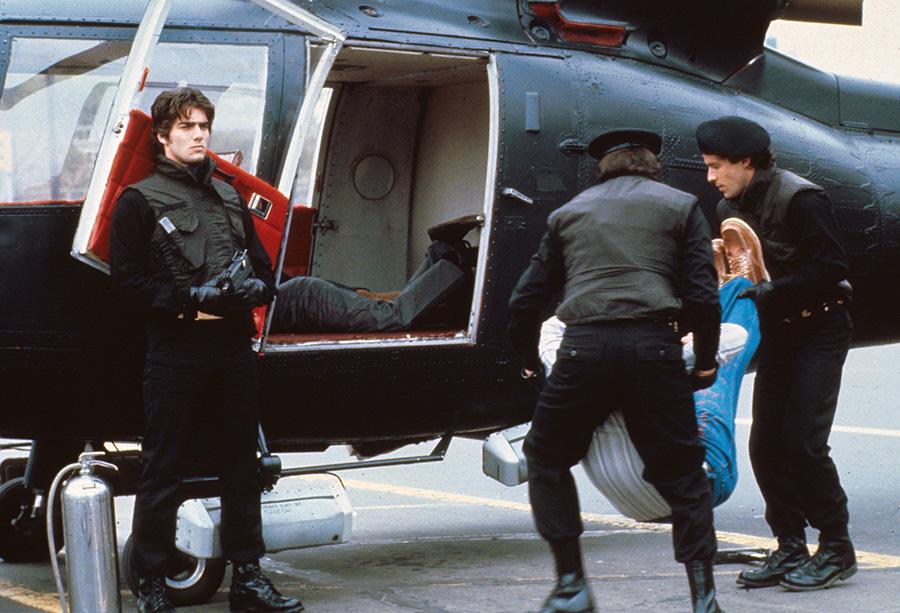 Zwei Söldner schaffen eine Leiche in einen schwarzen Helikopter. Im hinteren Bereich liegt bereits eine Leiche. Auf der linken Seite steht der bewaffnete Protagonist mit dem Rücken zum Hubschrauber.