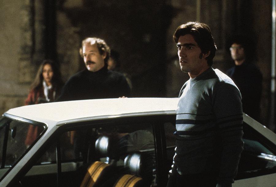 Der Protagonist steht im Vordergrund eines Autos und blickt nach links. Hinter dem Auto sind weitere Personen erkennbar. Unmittelbar hinter dem Kraftfahrzeug blickt ein Söldner in die selbe Richtung.