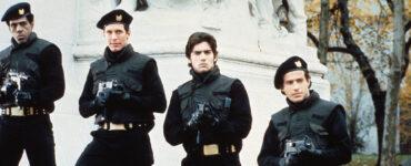 Vier Söldner in schwarzer Montur richten ihr Gewehr Richtung Kamera. Im Hintergrund ist ein massiver Sockel einer großen Statue erkennbar.
