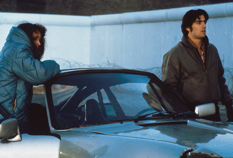 Der Söldner steht auf der Fahrerseite eines Autos auf der rechten Bildseite. Auf der Beifahrerseite lehnt sich eine Frau an das Dach des Autos. Beide blicken nach rechts.