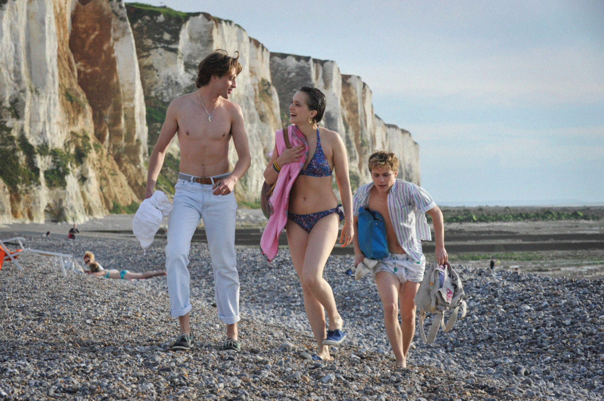 David flirtet am Strand in Sommer 85 offen mit Kate (Philippine Velge), während Alexis die Badesachen hinterherträgt.