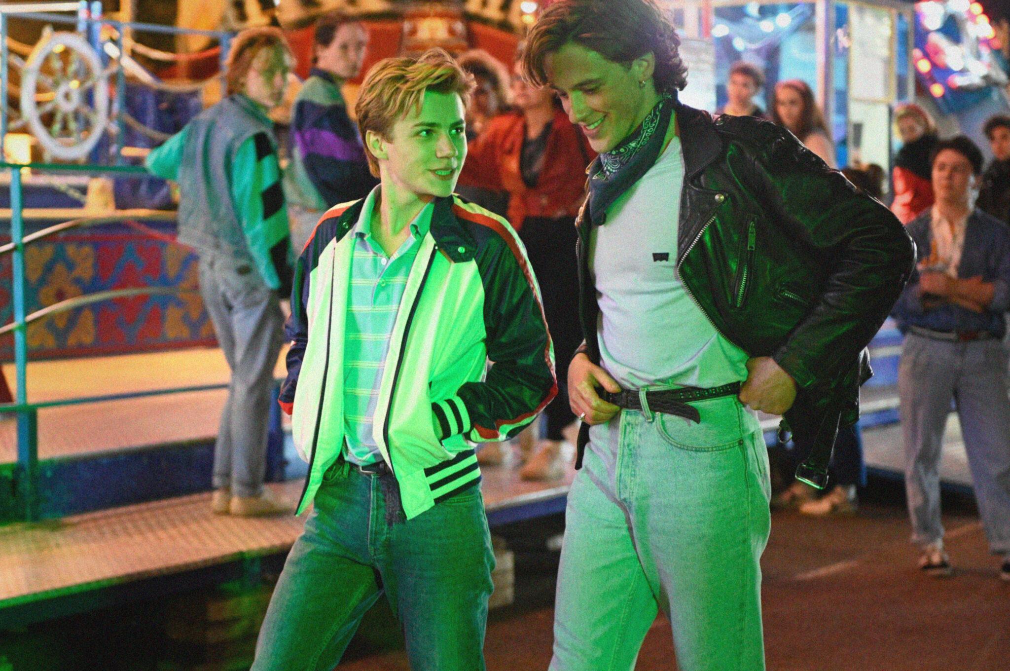 Alexis und David schlendern in Sommer 85 gutgelaunt über einen Jahrmarkt, von dessen grüner Beleuchtung sie angestrahlt werden.
