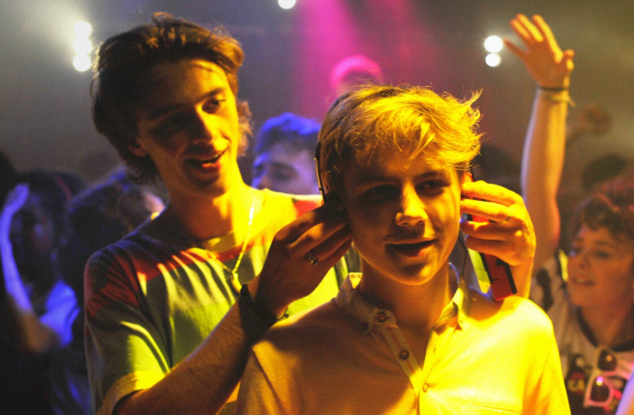 David setzt in Sommer 85 mitten in der Disco Alexis Kopfhörer auf. Im Hintergrund sieht man eine feiernde Meute.