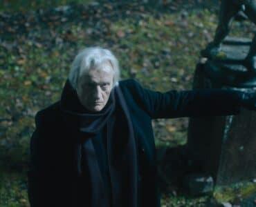 Richard Marlowe, gespielt von Rutger Hauer, weist mit ausgestrecktem Arm in Richtung einer alten Kapelle.