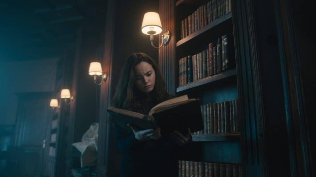 Rose, gespielt von Freya Tingley, steht in der Bibliothek ihres Vaters und liest in einem Buch.