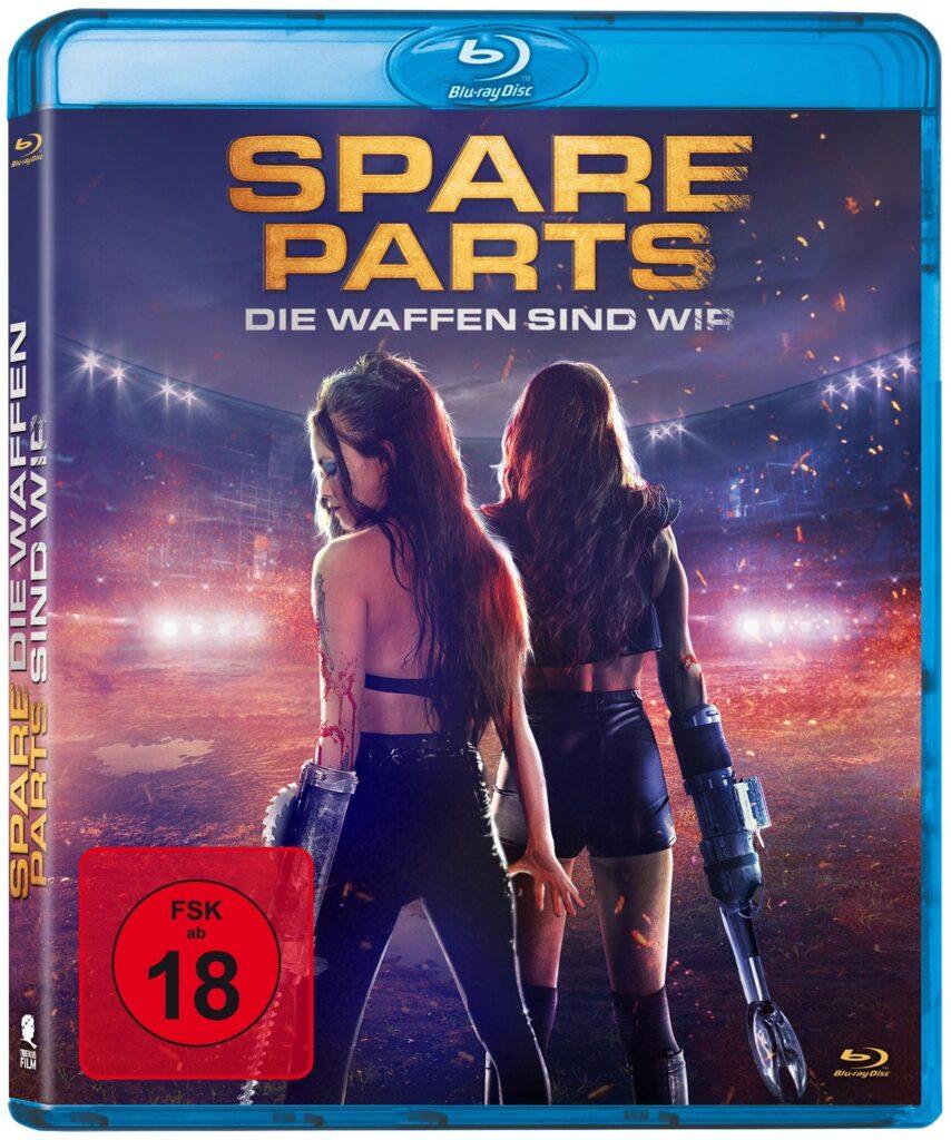 Zwei Mädels, beide haben eine Waffe statt eines rechten Arms, stehen mit dem Rücken zu uns, werden frontal geblendet - Spare Parts