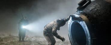 Konstantin schaut in Sputnik in seine Raumkapsel, während sich von hinten ein Mann im Nebel mit einer Taschenlampe nähert.