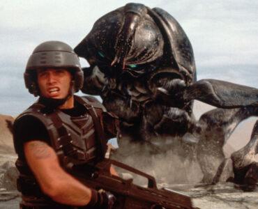 Johnny Rico (Casper van Dien) sieht sich einem riesigen Bug gegenüber. Dieser buddelt sich gerade aus der Erde, während der bewaffnete Rico sich von diesem abwendet und scheinbar warnend ruft. - Starship Troopers
