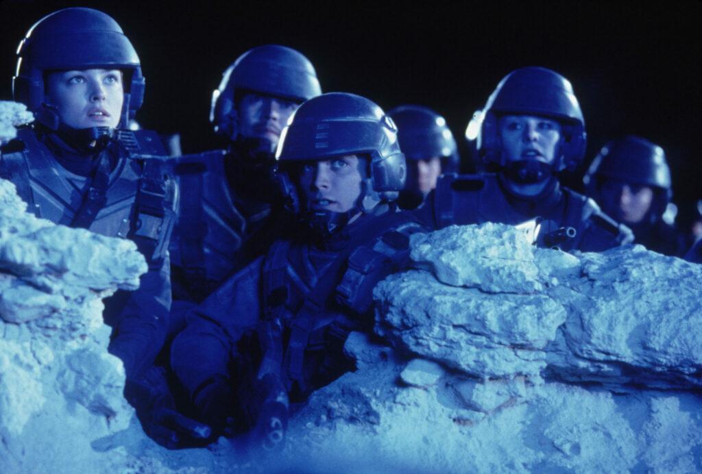 """Auf dem Bild sieht man die namensgebenden """"Starship Troopers"""", die sich im Dunklen hinter einer kleinen Felsformation befinden. Dabei beobachten sie etwas außerhalb des Bildes."""