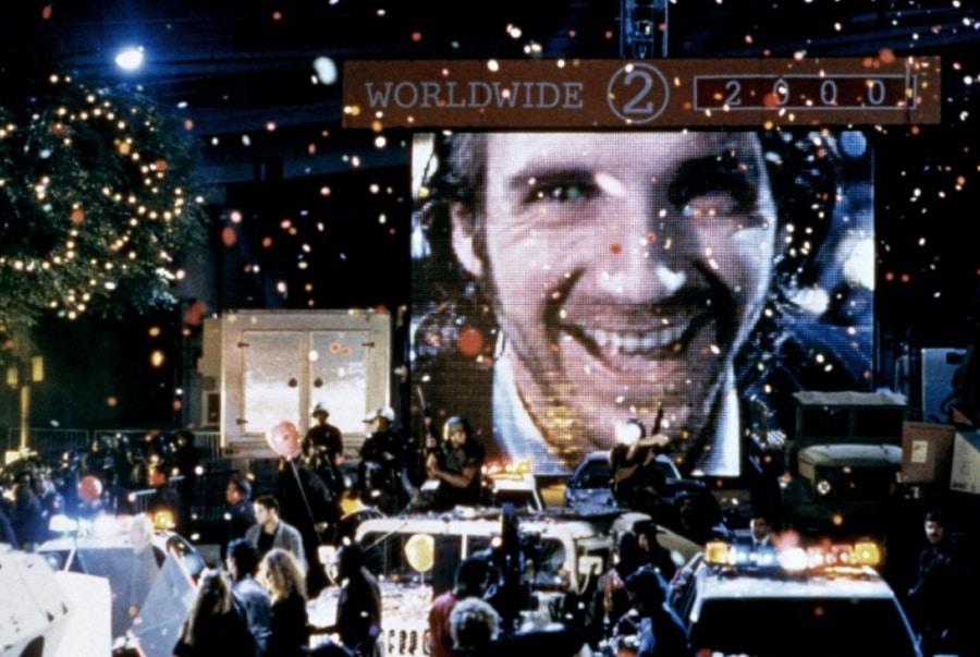 """Ralph Fiennes ist als Lenny Nero auf einem großen Bildschirm, der inmitten einer feiernden Menschenmenge steht, in """"Strange Days"""", einem der unbekannteren Filme der 90er, zu sehen."""