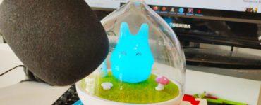 Eine leuchtende Figur steht auf einem Stapel Ghibli Filme. Davor ist ein Mikrofon und dahinter ein Laptop.