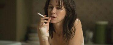 Naomi Watts sitzt mit einer Zigarette in der Hand auf der Couch.