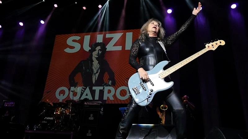 Eine alternde Suzi Quatro rockt die Bühne mit Bass und im Catsuit