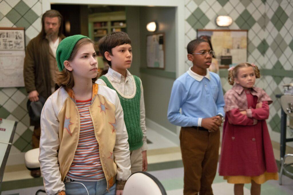 Die vier Waisenkinder (v.l.n.R.) Reynie, Sticky, Kate und Constance stehen grübelnd nebeneinander in einem Raum - in Die geheime Benedict-Gesellschaft © Disney