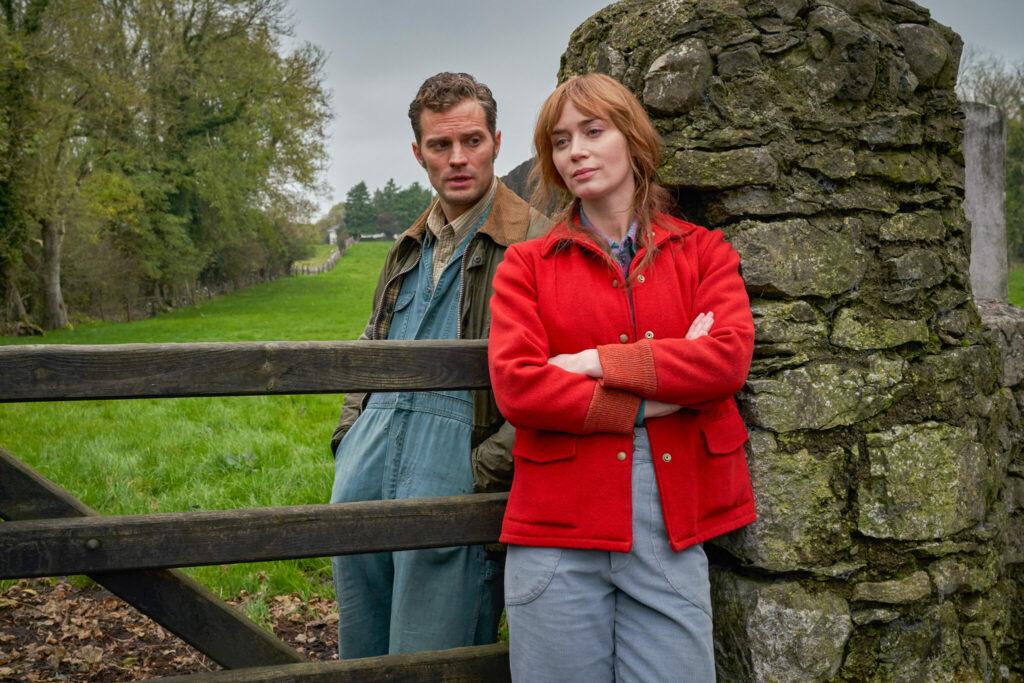 """Zu sehen sind Emily Blunt als Rosemary Muldoon und Jamie Dornan als Anthony Reilly bei einer Unterhaltung am Zaun in der """"Duft von wildem Thymian""""."""
