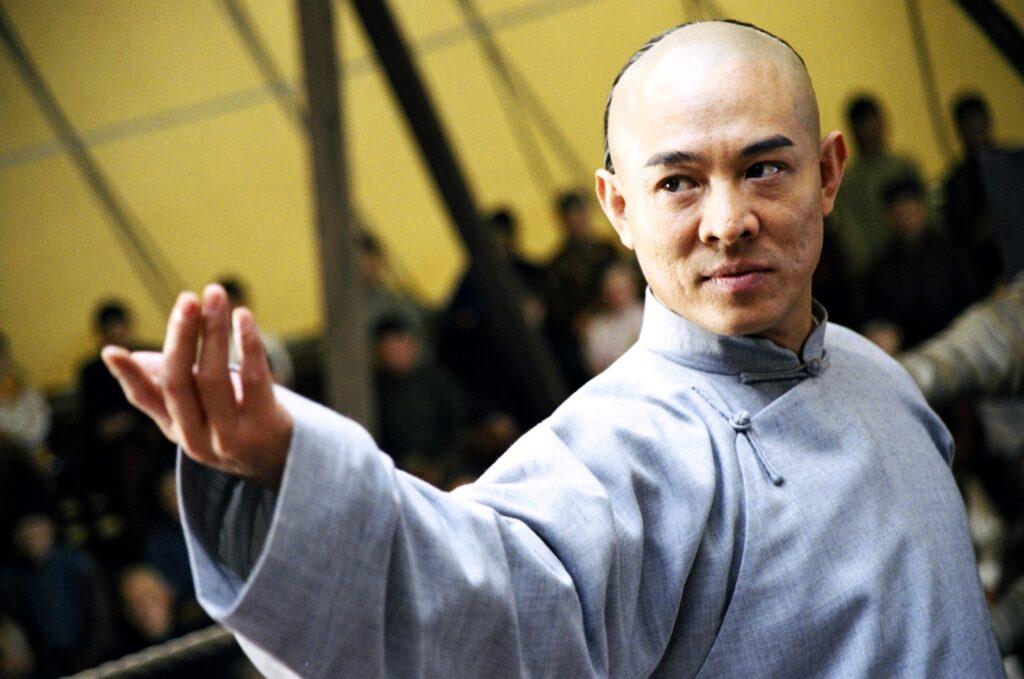 In einer Halbnahen ist Jet Li auf der rechten Bildseite erkennbar und streckt seinen rechten Arm zur Kampfpose aus. Im Hintergrund ist Publikum erkennbar.