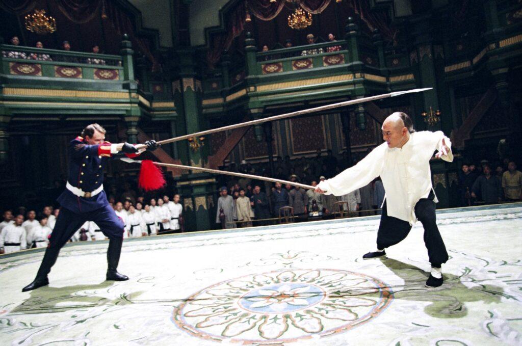 In einer Totalen bekämpft Huo Yuanjia seinen Gegner auf der linken Seite. Beide nutzen lange Speere. Die Kampfplattform zeigt ein auffälliges Kreisornament. Im Hintergrund steht das Publikum vor einer kunstvoll, in grüner Farbe dominierender Tribüne.