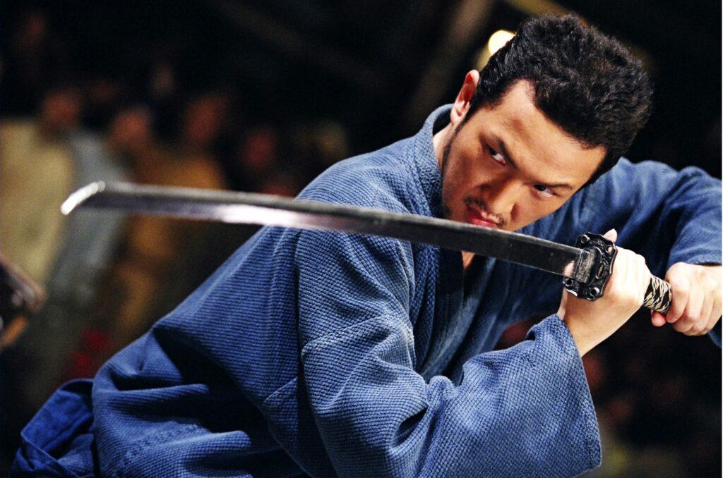 Ein Kampfkünstler in blauer Tracht nimmt eine zum rechten, oberen Bildrand verlaufende Diagonale ein und blict zur linken Seite zur Klinge seines horizontal nach vorne ausgerichteten Schwertes. Im Bildhintergrund ist Punlikum erkennbar