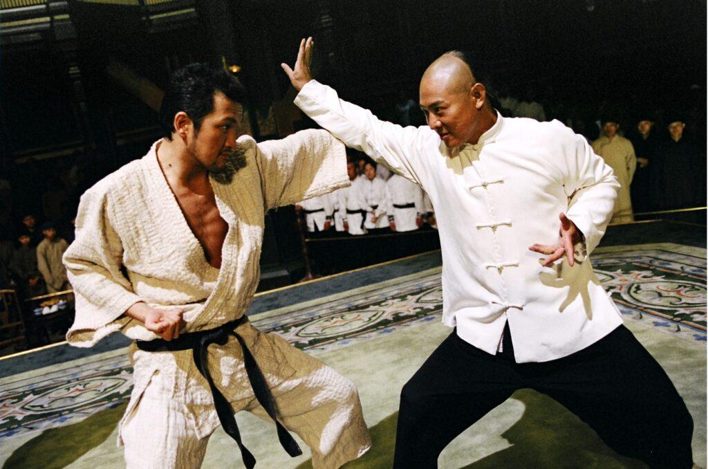 In der Amerikanischen Einstellungsgröße stehen sich Jet Li auf der rechten Seite und sein Gegner gegenüber und bekämpfen sich. Im Bildhintergrund schauen Kampfkünstler dem Geschehen zu.