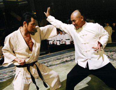 In der Amerikanischen Einstellungsgröße stehen sich Huo Yuanjia auf der rechten Seite und sein Gegner gegenüber und bekämpfen sich. Im Bildhintergrund schauen Kampfkünstler dem Geschehen zu.