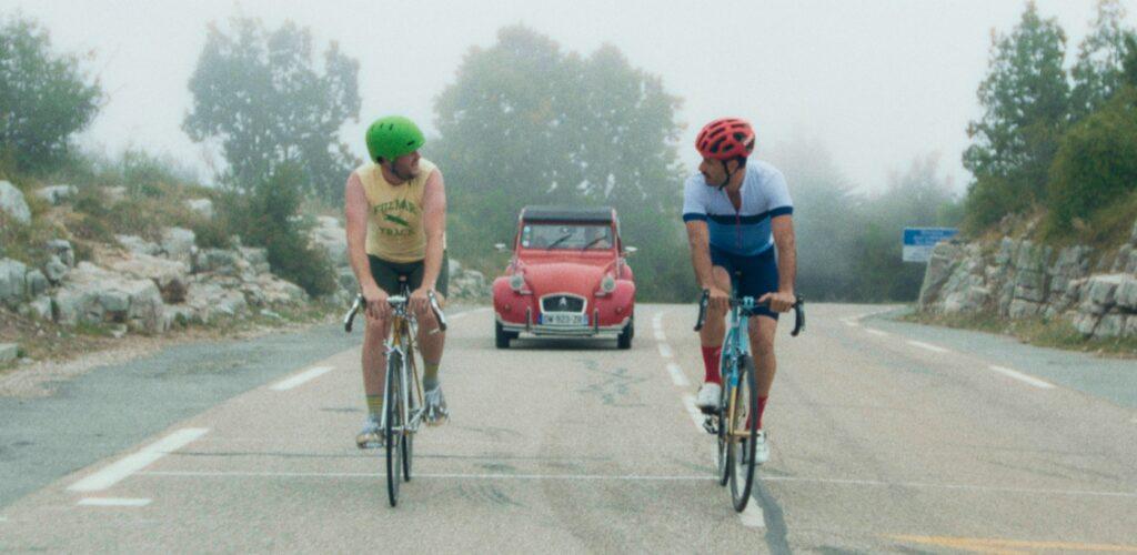 Die Freunde Mike und Kyle blicken während der Fahrradtour in The Climb einander an. Hinter ihnen nähert sich ein rotes Auto.